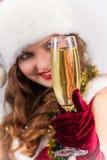 女孩在有香槟玻璃的圣诞老人帽子 库存照片