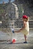 女孩在有水喷水隆头的热的夏天城市 库存照片