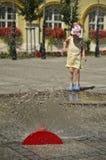 女孩在有水喷水隆头的热的夏天城市 免版税库存照片