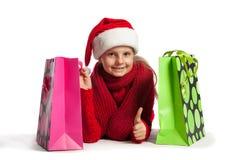 女孩在有购物袋的圣诞老人帽子 免版税库存图片