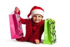 女孩在有购物袋的圣诞老人帽子 免版税图库摄影