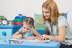 女孩在有统治者的一个笔记本画,老师帮助她 库存图片