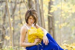女孩在有mapple花束的秋天森林离开 库存照片