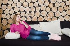 女孩在木背景的沙发放置 免版税库存图片