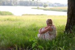 女孩在树坐 免版税库存图片