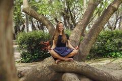 女孩在树思考在公园 库存图片