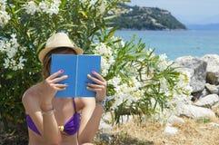 女孩在树荫下的读一本书在与岩石的海滩附近在背景中 免版税图库摄影