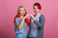 女孩在桃红色背景加入了手并且做了心脏 免版税库存图片