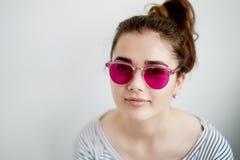 女孩在桃红色玻璃愉快地微笑 世界的一个天真看法在转折的与成年 免版税库存图片