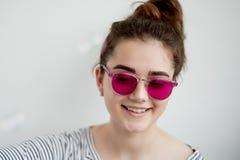 女孩在桃红色玻璃愉快地微笑 世界的一个天真看法在转折的与成年 库存图片
