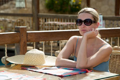 女孩在桌上坐大阳台 图库摄影