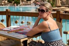 女孩在桌上坐游泳池边大阳台 免版税库存图片