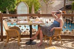 女孩在桌上坐游泳池边大阳台 库存图片