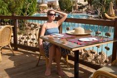 女孩在桌上坐游泳池边大阳台 库存照片