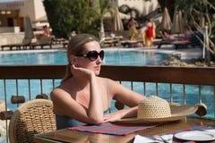 女孩在桌上坐游泳池边大阳台 免版税库存照片