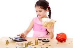 女孩在桌上计数金钱 图库摄影