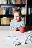 女孩在桌上,在弄皱一张纸的手上 库存照片
