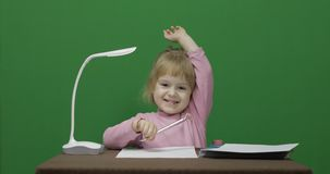 女孩在桌上 因为她认识答复对问题,举她的手 免版税图库摄影