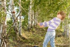 女孩在桦树树丛里 免版税库存照片