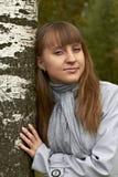 女孩在桦树t树的树干附近与金黄头发佩带的玻璃的投入了她的胳膊在明亮的围巾凉快的夏天轻微的微笑 库存图片