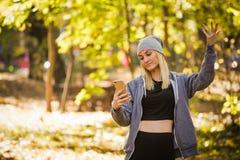 女孩在森林里丢失了一个流动信号,并且不可能传送信息 免版税库存照片