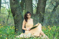 女孩在森林里读一本书。 免版税库存照片