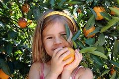 女孩在橙色树丛里 免版税库存图片