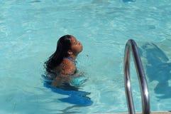 女孩在水中沉浸于在以后的每年游泳体育比赛的严谨训练以后 免版税图库摄影