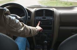 女孩在汽车的轮子后去并且交换在汽车的音乐 驾驶汽车关闭  库存图片