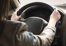 女孩在汽车的轮子,在方向盘的手后去 驾驶一辆大汽车 库存图片