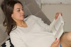 女孩在沙发教育的阅读书 库存照片