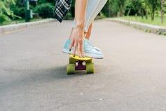 女孩在沥青的一个滑板乘坐并且拿着平衡 免版税库存照片