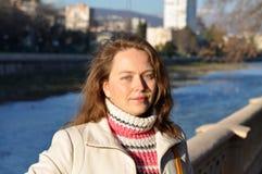 女孩在河堤防站立 免版税图库摄影