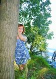 女孩在河岸的一棵树旁边站立夏天下午 免版税库存照片