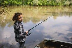 女孩在河抓鱼 免版税库存照片