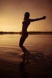 女孩在河跳在日落 免版税库存图片