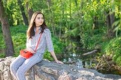女孩在河附近坐 免版税图库摄影