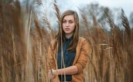 女孩在沼泽草厚实的丛林结冰  免版税图库摄影