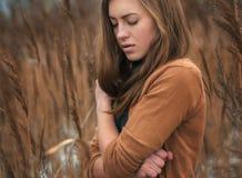 女孩在沼泽草厚实的丛林结冰  库存图片