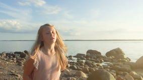 女孩在海岸旁边今后跑并且看 股票视频