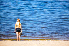 女孩在海岸站立 免版税库存照片