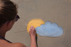 女孩在海滩云彩,太阳,天气预报,心情的沙子画 多云部分 免版税库存图片
