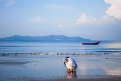 女孩在海滩和小船视图的戏剧沙子 库存图片