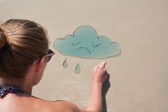 女孩在海滩的沙子画云彩 天气预报,心情 多云,阴云密布 免版税库存图片