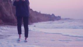 女孩在海的湿沙子走在黎明并且接触从波浪的泡沫 影视素材