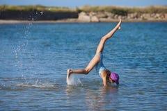 女孩在海运做手倒立 免版税库存照片