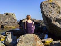 女孩在海附近实践瑜伽,岩石的,慢动作hd录影 库存照片