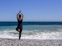 女孩在海附近实践瑜伽,慢动作hd录影 库存图片