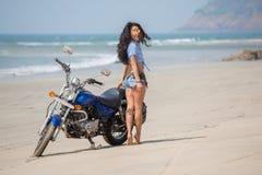 女孩在海滩的一辆摩托车附近站立 免版税库存照片