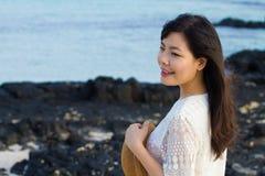 女孩在海滩的岩石站立 库存图片